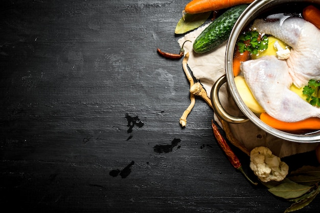 Not boiled chicken soup with fresh vegetables and spices. on a black wooden background.