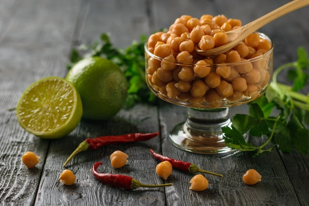 Boiled chickpeas in a glass bowl, pepper, herbs and lime on a wooden table.