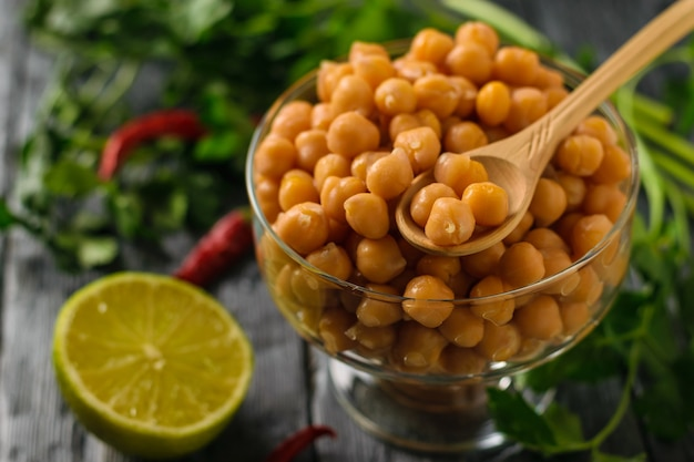 Boiled chickpeas in a glass bowl, pepper and lime on a table. vegetarian cuisine from legumes.