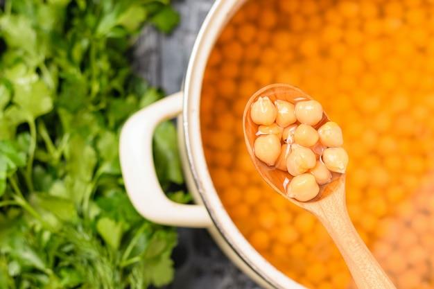 木のスプーンと暗いテーブルの上の鍋でひよこ豆をゆでた。マメ科植物からのベジタリアン料理。上からの眺め。