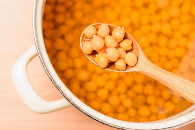 ひよこ豆を木のスプーンと黄色いテーブルの上の鍋で茹でた。マメ科植物からのベジタリアン料理。上からの眺め。