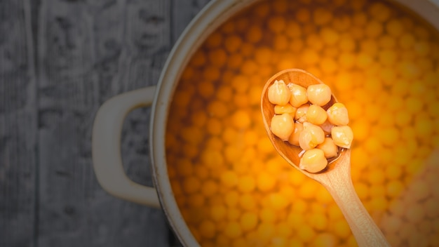 Boiled chickpeas in a wooden spoon. vegetarian cuisine from legumes. the view from the top.