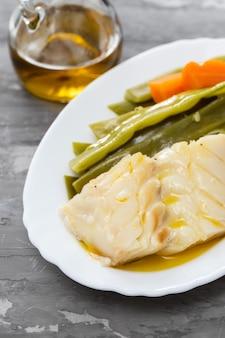 Вареная треска с овощами на белом блюде
