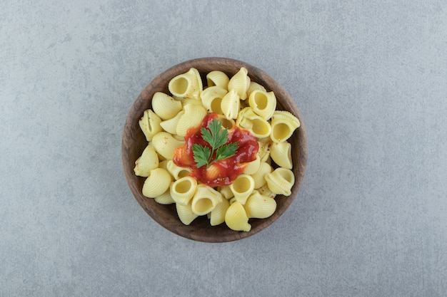 Boiled conchiglie pasta with ketchup in wooden bowl.