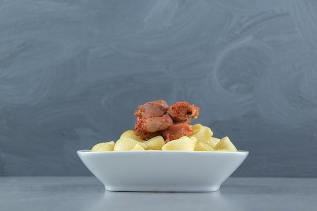 白い皿に肉をマリネしたコンキリエのゆでパスタ。