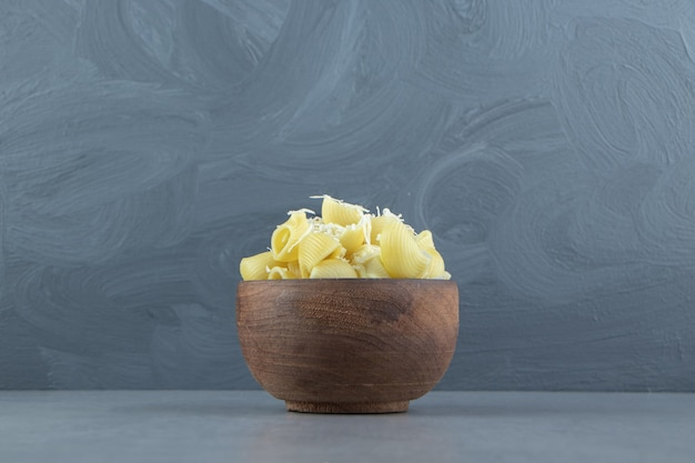Boiled conchiglie pasta in wooden bowl.