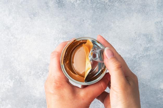 ブリキ缶で練乳を茹でたもの。朝食とデザートに甘いパスタが広がります。スペースをコピーします。 Premium写真