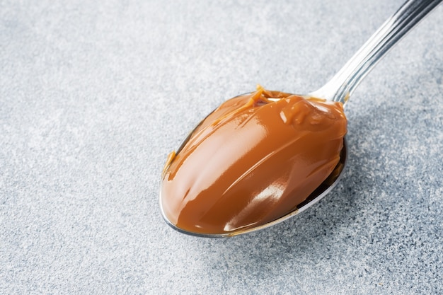 Boiled condensed milk in a spoon. sweet pasta spread for breakfast and dessert. copy space.