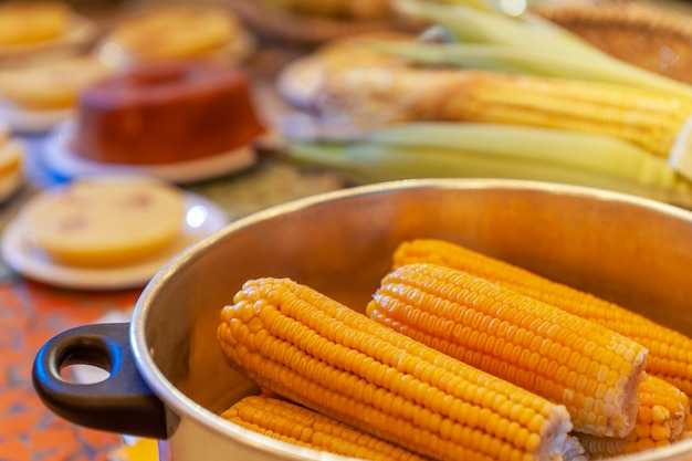 Boiled corn in the aluminum pan on a table with other foods
