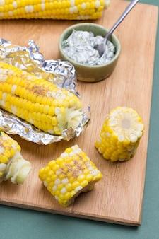 Вареная кукуруза и вареная кукуруза в фольге на деревянной доске. зеленый фон. закрыть вверх