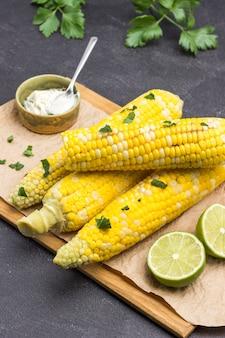 Вареная кукуруза на деревянной доске. лайм и соус в миске. листья петрушки. черный фон. вид сверху