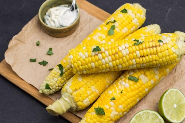 Вареная кукуруза на деревянной доске. соус в миске. листья петрушки. черный фон. вид сверху