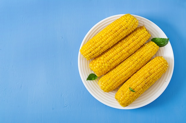Boiled corn in white plate on blue table. summer food. top view. flat lay