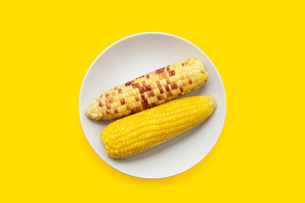 Boiled corn in white plate on yellow background.