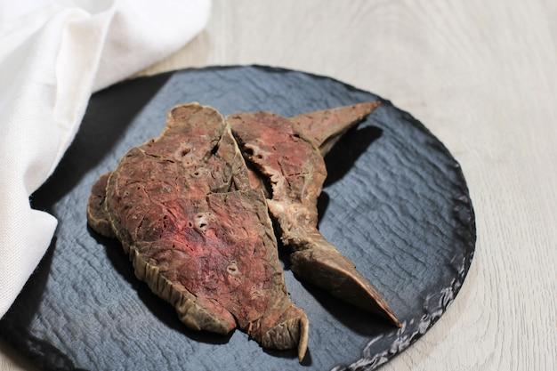 木製のまな板で茹でた牛の肺、調味料や調理の準備ができて