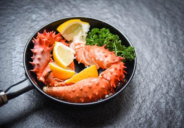 삶은 게 발톱 요리 냄비에 레몬 파 슬 리 허브와 향신료와 알래스카 킹 크랩 해산물 팬 어둡고 붉은 게 홋카이도