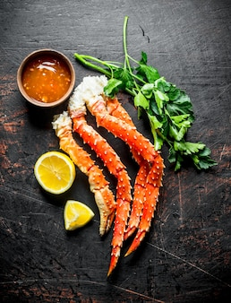 Boiled crab with herbs, sauce and sliced lemon. on dark rustic background