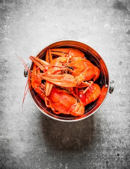 Boiled crawfish in a steel bucket on concrete.