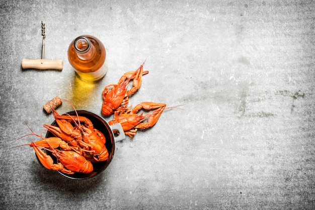 Boiled crawfish with a bottle of white wine and slices of lemon on concrete.