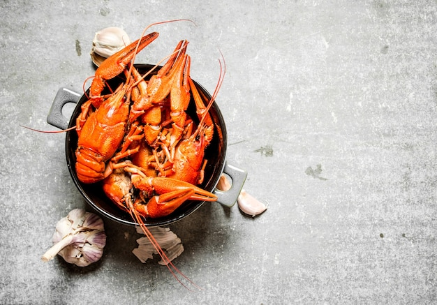Boiled crawfish with garlic on concrete.