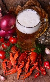 Вареные раки и пиво на деревянных фоне