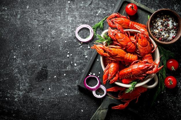 양파 링, 토마토, 향신료와 함께 커팅 보드에 삶은 왕새우. 어두운 소박한 배경에