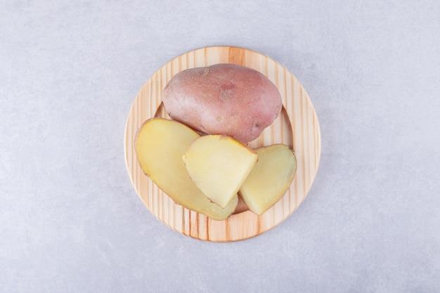 Patate deliziose bollite sul piatto di legno.