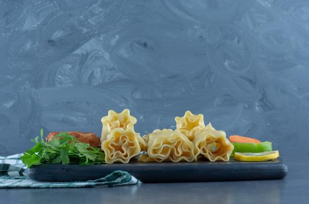 Rotoli di pasta bolliti e pollo arrosto su tavola scura.