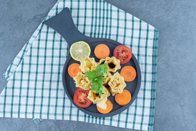 Panini e verdure bolliti della pasta sul bordo scuro.
