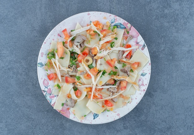 Вареное тесто с нарезанными овощами на красочной тарелке.