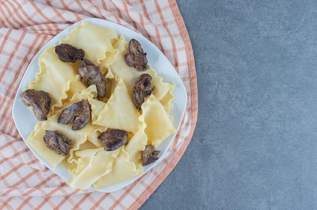 흰 접시에 말린 고기 부분을 넣은 삶은 반죽.