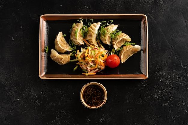 신선한 야채, 양배추, 무, 당근, 오이, 파, 참깨 간장으로 삶은 만두.
