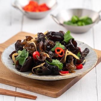 Вареные съедобные древесные черные грибы, деревянное ухо в тарелке на белой поверхности стола.