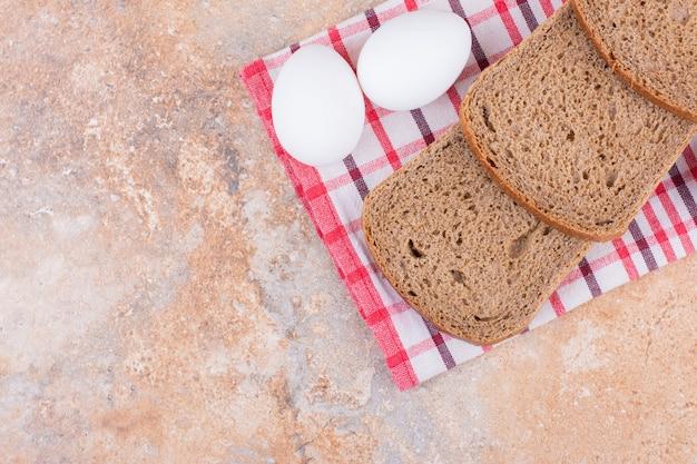 대리석 배경에 티 타월에 삶은 계란과 빵.