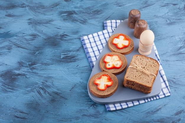 Вареное яйцо и нарезанный хлеб на доске на кухонном полотенце, на синем столе.