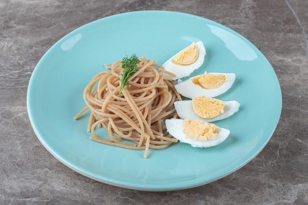 Вареное яйцо и спагетти на синей тарелке.