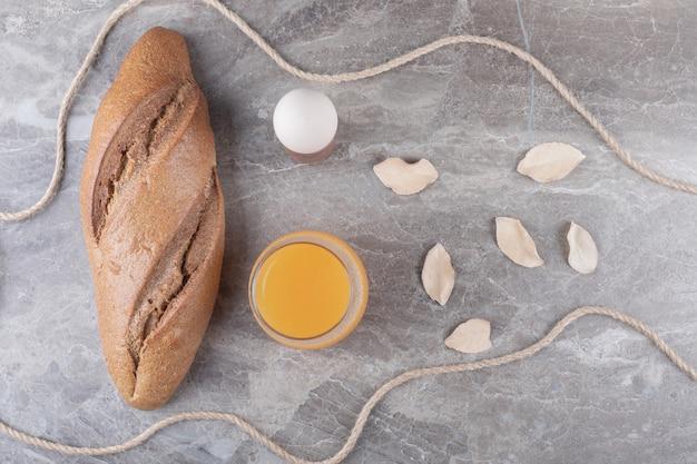 大理石の背景にゆで卵、パン、ジュースのガラス。