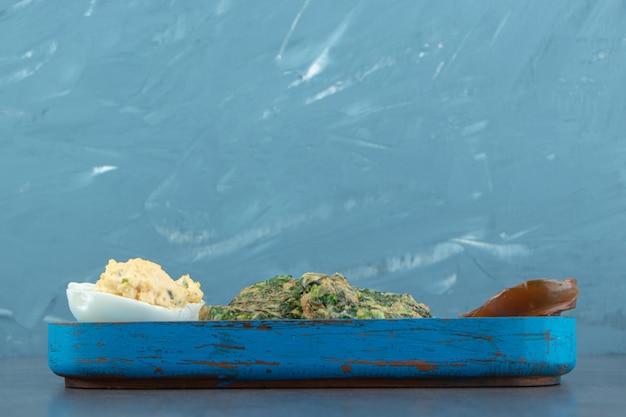 Uovo sodo e uovo fritto con verdure sul piatto blu.