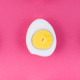 Boiled egg half on pink table