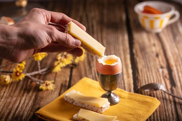 나무 테이블에 빵과 치즈와 은색 껍데기에 삶은 계란