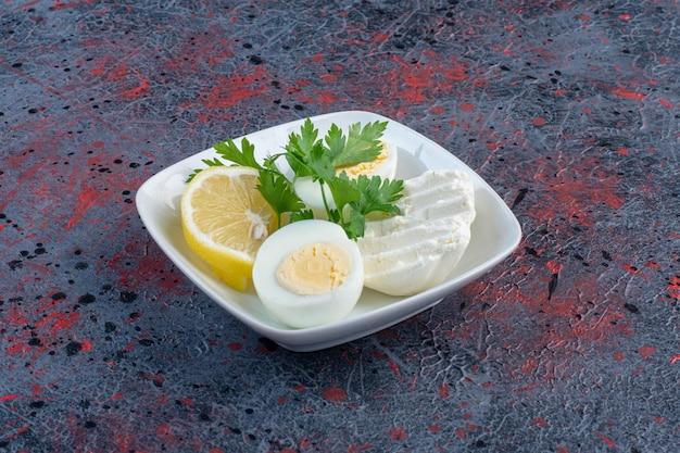 チーズとハーブを添えた白い皿にゆで卵。