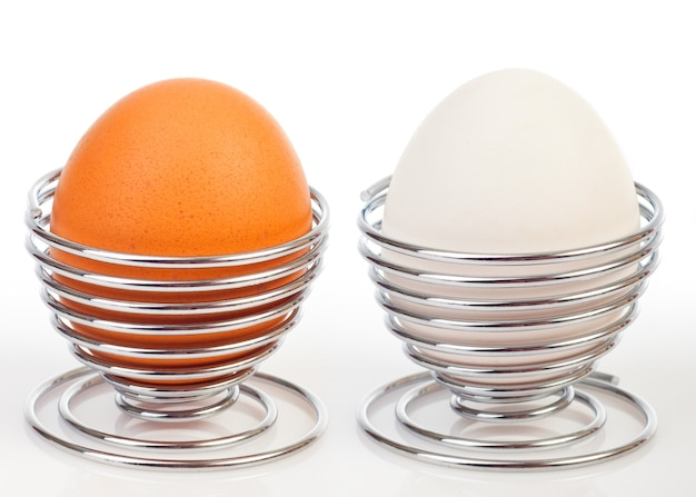 Boiled egg isolated on white in chrome egg cup