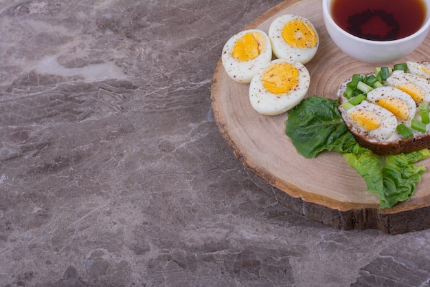 Boiled egg sandwich with a cup of tea on a wooden board.