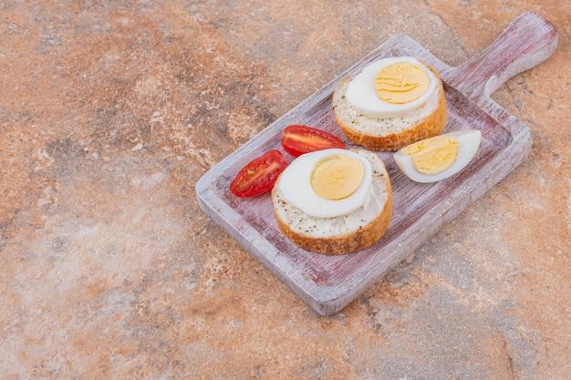 대리석 위에 보드에 삶은 계란, 토마토 및 빵.