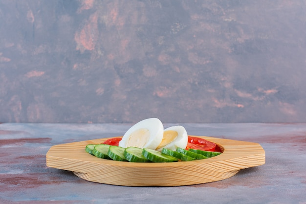 Boiled egg, tomatoes and cucumber in a wooden plate on the marble surface