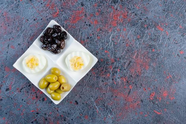 Uovo sodo con olive marinate nere e verdi.