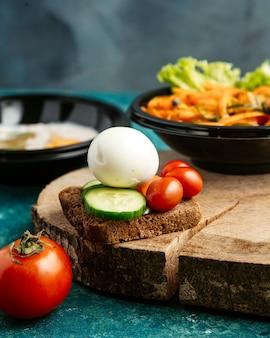 ゆで卵とキュウリのトマトと茶色のパンのスライス