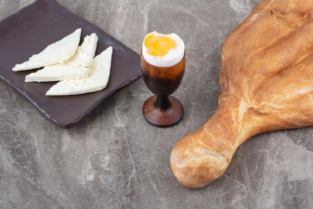 大理石の背景に焼きたての白パンとゆで卵。高品質の写真