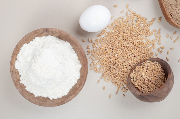 Boiled egg with oat grains and wooden bowl full of flour