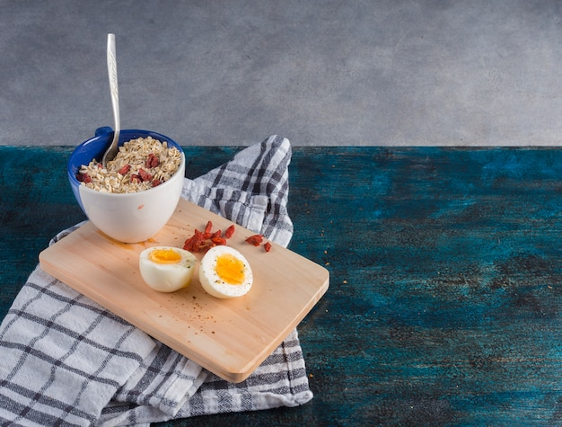 Boiled egg with oatmeal on wooden board